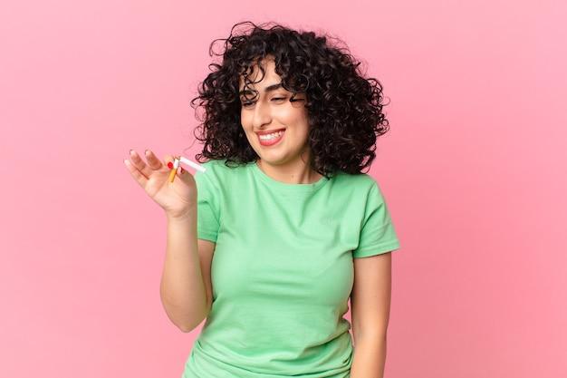 예쁜 아랍 여성이 행복하게 웃고 공상을 하거나 의심합니다. 금연 개념