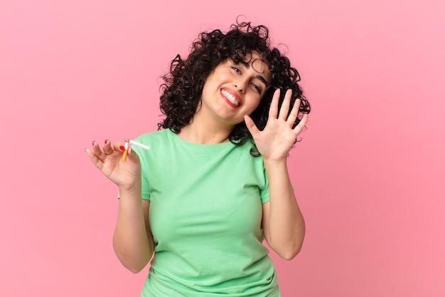 예쁜 아랍 여성이 행복하게 웃고 손을 흔들며 환영하고 인사합니다. 금연 개념
