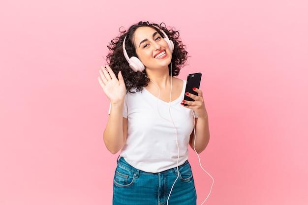 Довольно арабская женщина счастливо улыбается, машет рукой, приветствует и приветствует вас в наушниках и смартфоне