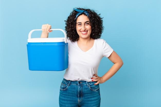 예쁜 아랍 여성은 엉덩이에 손을 대고 행복하게 웃고 있으며 휴대용 냉장고를 들고 있습니다.