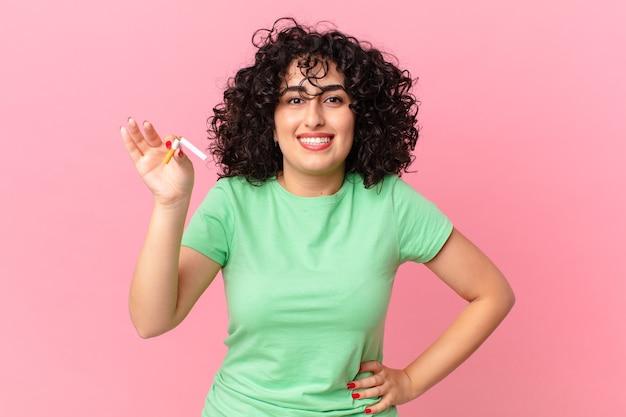 엉덩이에 손을 대고 행복하게 웃고 있는 예쁜 아랍 여성. 금연 개념