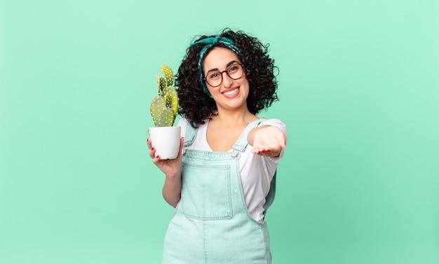 フレンドリーで幸せそうに笑って、コンセプトを提供し、鉢植えのサボテンを持っているかなりアラブの女性