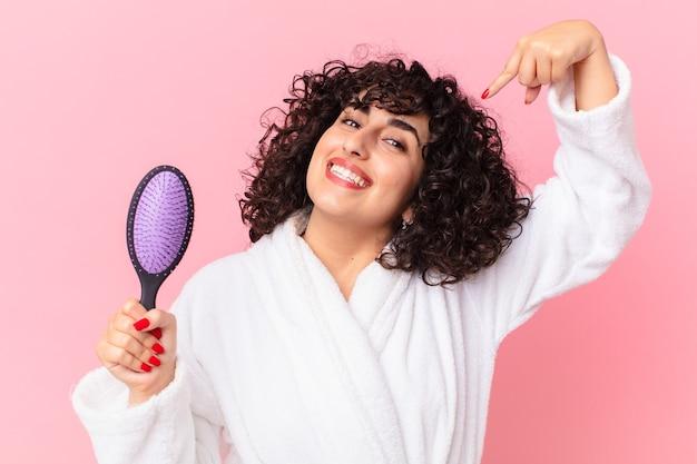 バスローブを着てヘアブラシを持っているかなりアラブの女性