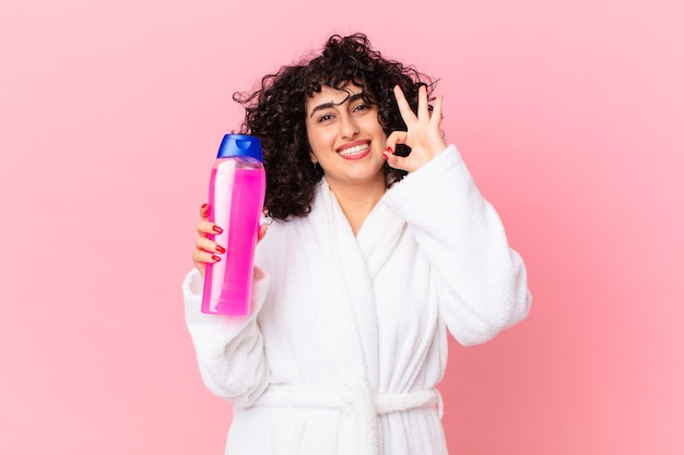 バスローブを着てシャンプーボトルを持っているかなりアラブの女性