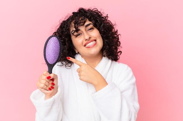 Pretty arab woman wearing bathrobe and holding a hairbrush