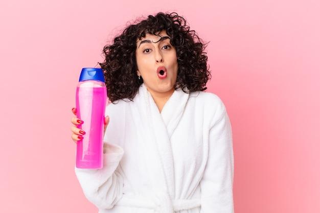 Pretty arab woman wearing bathrobe and holding a shampoo bottle