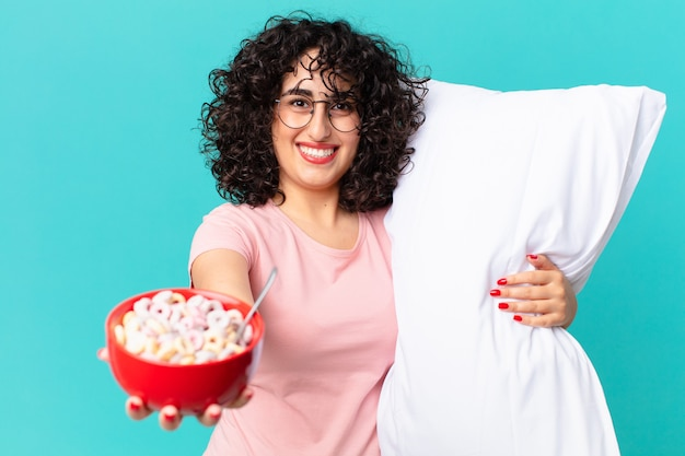 パジャマと枕を身に着けているかなりアラブの女性。