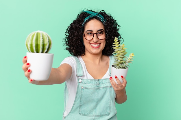 装飾的な鉢植えのサボテンを持つかなりアラブの女性
