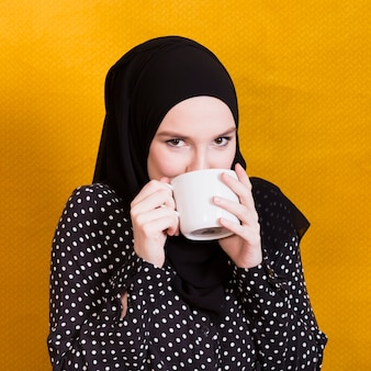 Pretty arabian woman drinking beverage in cup against surface