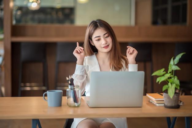 Довольно азиатская деловая женщина разговаривает и видеоконференцсвязь на портативном компьютере в офисе