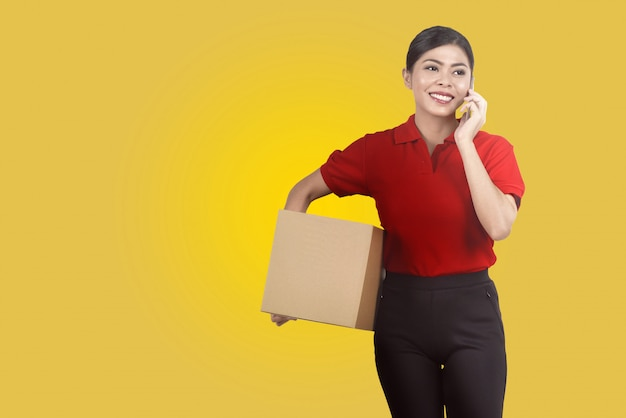 Pretty asian female courier using mobile phone while holding parcel