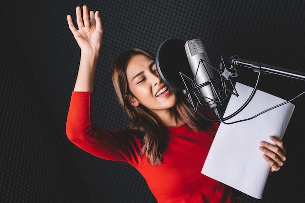 음악 녹음 스튜디오에서 열정으로 스튜디오 마이크와 팝 방패를 사용하여 노래를 녹음하는 예쁜 아시아 여성 가수.