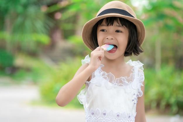더운 여름에 아이스크림을 먹는 꽤 아시아 여자 아이
