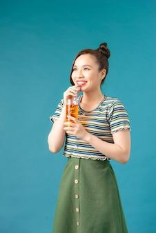 청량 음료 한 잔을 마시는 꽤 아시아 여자