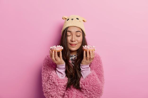 예쁜 아시아 소녀는 갓 구운 맛있는 도넛에서 즐거운 냄새를 즐기고 맛있는 도넛으로 유혹하고 다이어트 딜레마가 있으며 분홍색 코트를 입고 있습니다.
