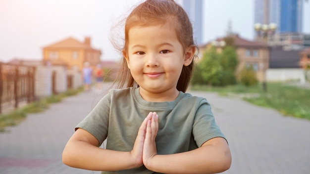 Pretty asian girl holds hands in pray gesture on waterfront