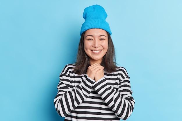 La ragazza abbastanza asiatica tiene le mani insieme guarda con un sorriso gentile alla macchina fotografica ha soddisfatto l'espressione del viso sente qualcosa di piacevole