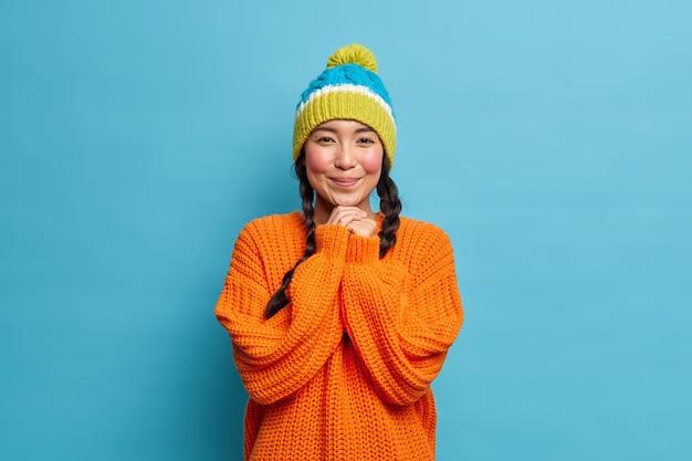 可愛らしいアジアの女の子は、彼氏から褒められて、あごの下で手を赤く恥ずかしがり屋にしています。暖かいニットのセーターを着ており、帽子は青い壁に隔離された魅力的な視線を持っています