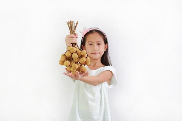 白い背景の上にあなたに与えるリュウガンの果実の束を保持しているかなりアジアの女の子の子供。彼の手で果物に焦点を当てる