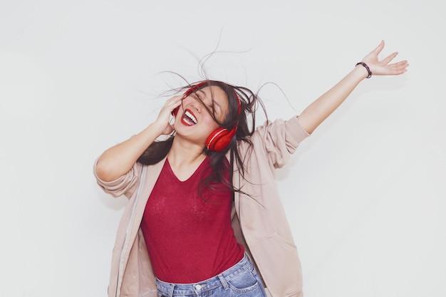 Музыка довольно азиатской девушки слушая с красными наушниками на белой предпосылке.
