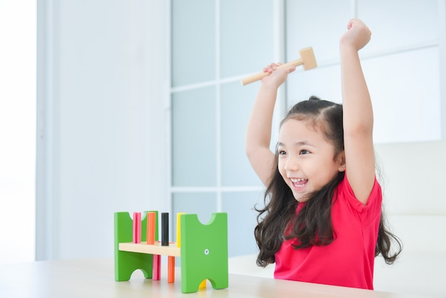 Pretty asian girl raising hands up happily while playing toy at home