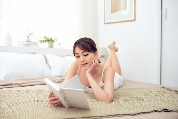 ベッドに横たわって朝と本を読んでかわいいアジアの女の子