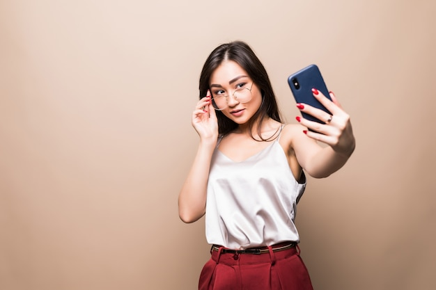 Pretty asian girl take selfie with her smart phone isolated on beige wall.