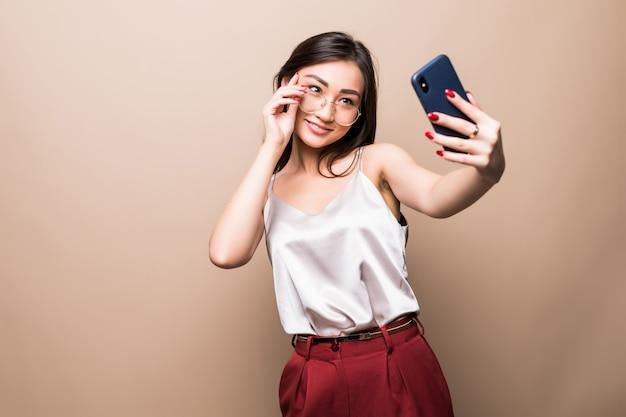 かなりアジアの少女は、ベージュの壁に分離された彼女のスマートフォンでselfieを取る。