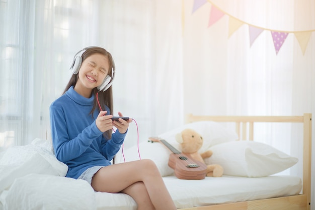 Pretty asian girl using headphone for listen music by smartphone on the bed in her decorat