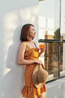 ビンテージ ドレスを着て、壁の後ろにオレンジ ジュースの帽子をかぶっているかなりアジアの女の子