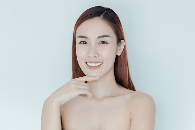Pretty asian girl with big eyes and dark eyebrows, with naked shoulders, beautiful woman looking at camera and smiling