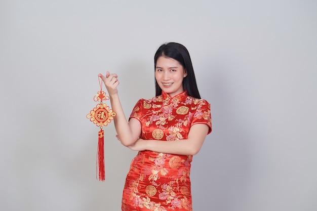 Довольно азиатская девушка с китайской традиционной одеждой cheongsam или qipao, держащей фейерверк. концепция китайского нового года, женская модель, изолированные на сером фоне студии