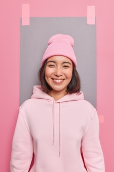 Симпатичная азиатская девушка с нежной улыбкой и позитивным настроем носит толстовку и шляпу, рада слышать хорошие новости, позирует на фоне розовой стены, оштукатуренного серого листа бумаги, чтобы написать свою информацию.