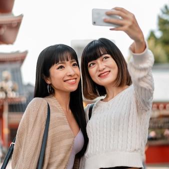 Довольно азиатские девушки вместе делают селфи
