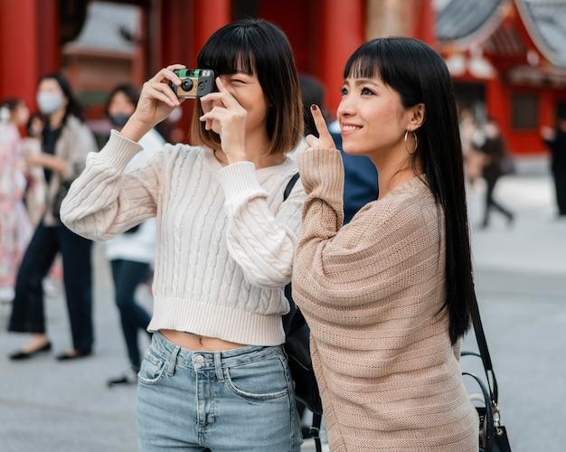 Ragazze abbastanza asiatiche che scattano foto in vacanza