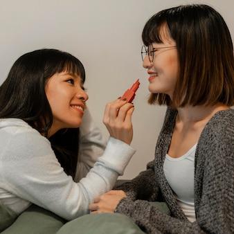 Ragazze abbastanza asiatiche che provano i prodotti di trucco
