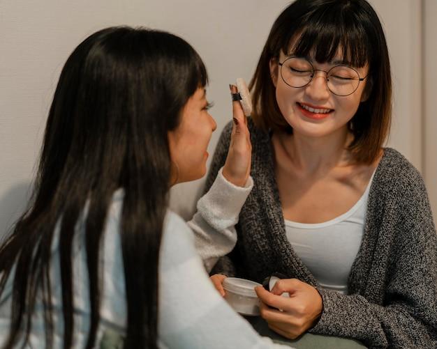 Довольно азиатские девушки пробуют продукты для макияжа