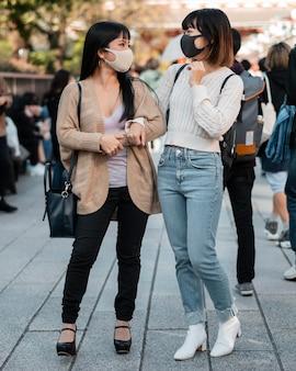 Ragazze abbastanza asiatiche che indossano maschere per il viso