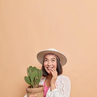위에 초점을 맞춘 세련된 옷을 입은 예쁜 아시아 여성은 화분에 담긴 선인장을 들고 행복한 표정을 짓고 있습니다