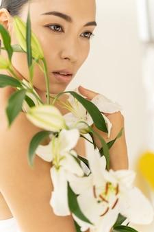 예쁜 아시아 여성이 아름다운 꽃다발을 들고 있다