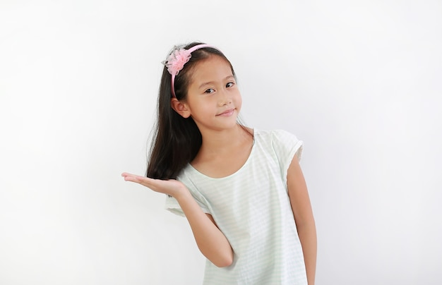 Pretty asian little girl child with hand holding long black hair and looking at camera over white background