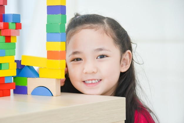 Pretty asian little girl playing with colorful wood blocks at home