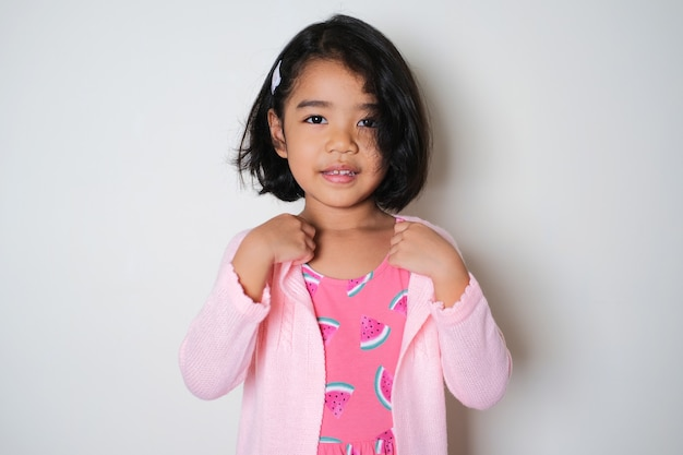 Pretty asian little girl wearing pink cardigan and showing confident expression
