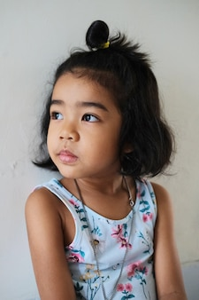 Pretty asian little kid looking toward light with white wall as background