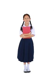 태국 교복을 입은 예쁜 아시아 여학생이 흰색 배경에 격리된 책을 껴안고 서 있습니다. 클리핑 패스가 있는 전체 길이