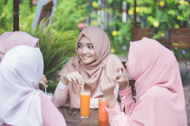 Pretty asian muslim woman having fun in cafe together with friends