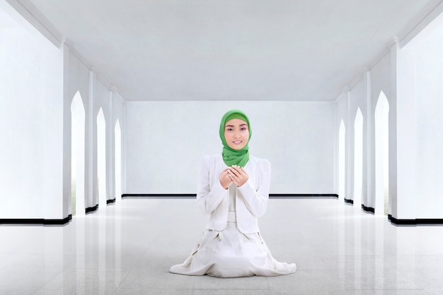 Pretty asian muslim woman praying to god