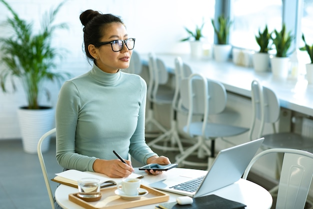 Довольно азиатский студент в очках и повседневном пуловере сидит за столом перед ноутбуком и делает заметки в блокноте