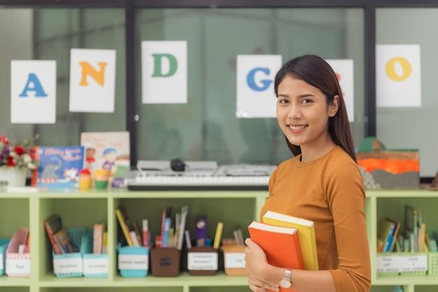小学校の教室の後ろにカメラで笑みを浮かべているかなりアジアの先生。ヴィンテージエフェクトスタイルの写真。
