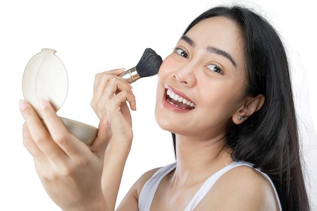 Довольно азиатская женщина наносит макияж с помощью кисти, глядя в камеру